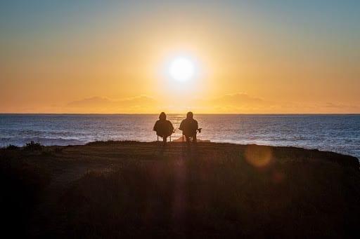 Couple enjoying retirement lifestyle watching sunset at the beach.